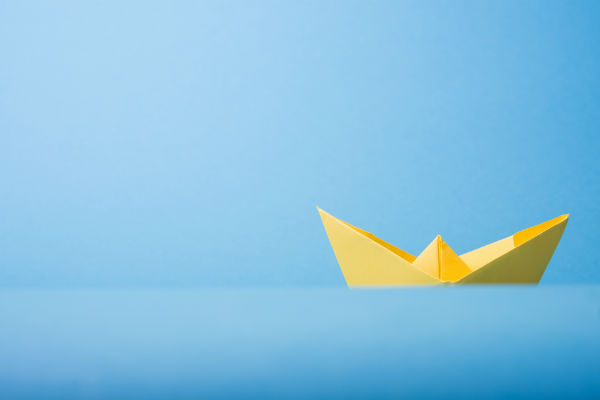 Paper boat against blue background